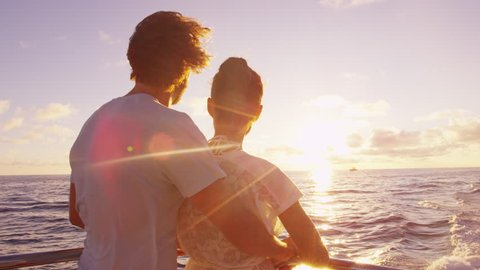 Cruise ship vacation couple enjoying sunset view sailing on small cruise boat at sea. Romantic couple on honeymoon travel at sea looking at sunset.  SLOW MOTION.