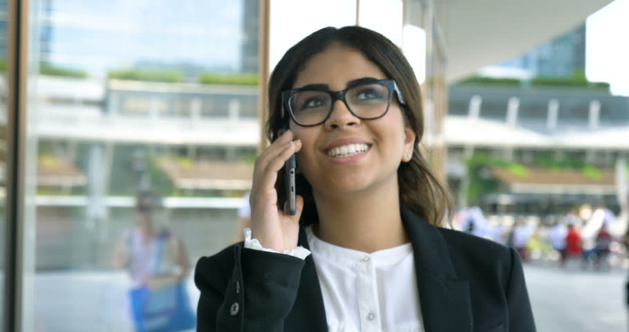 Portrait of a young beautiful business woman (student) in a suit, glasses, sitting at the table, talking on the phone, writing a message. Concept: new business, communication, Arab, banker, manager. #28148797