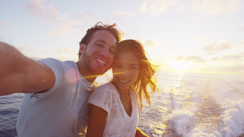 Selfie video - Romantic couple taking selfie video by sunset over the ocean on small cruise ship sailing on open sea. Woman and man taking cell phone photos on boat travel sailing during vacation. | Shutterstock HD Video #28149055