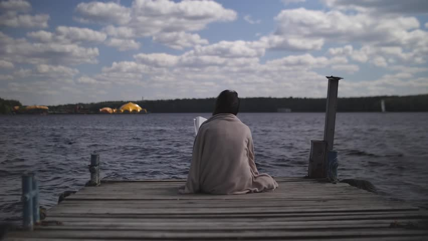 Brunette in blanket sits on old wooden pier and reads a book against the background of water and forest