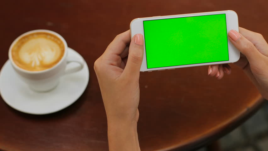Female hands holding white smartphone with green screen on wooden backgroung in the cafe. Horizontal. Woman drinking coffee. Close up. Chroma key. | Shutterstock HD Video #28161415