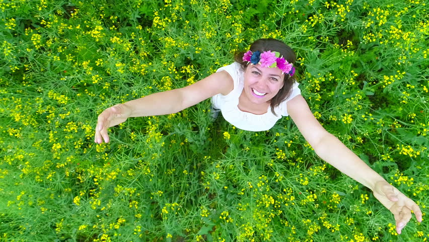 Happy woman in rape field, aerial rotating top view