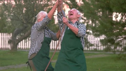 Couple having fun, water hose. Cheerful senior people outdoors. You are never too old.