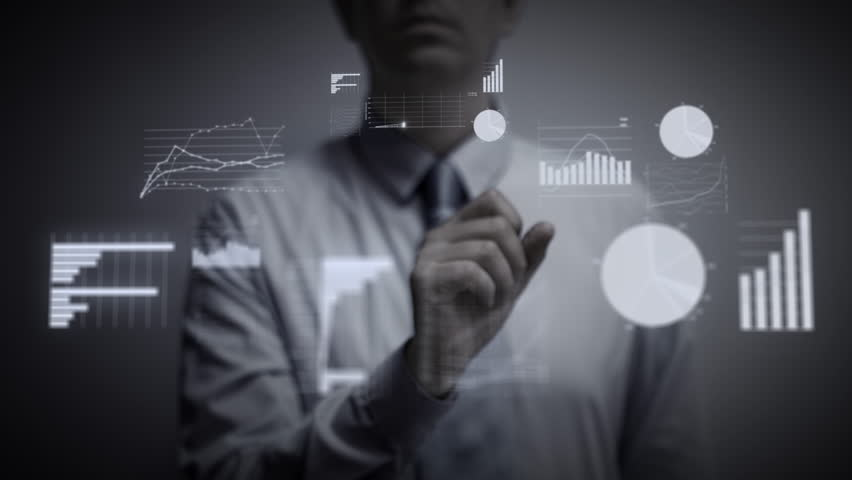 A businessman working on a blue holographic interface, touching a hologram showing a visual screen with computer and business icons. Financial charts and graphs appear. The touchscreen illuminates. 4K | Shutterstock HD Video #28185526