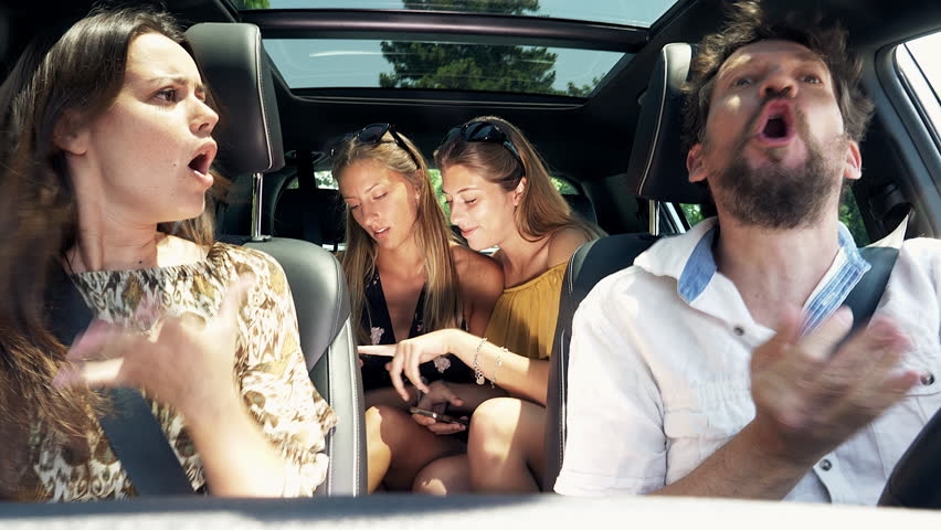 Father and mother fighting driving car while daughters in back seat laugh with cell phone