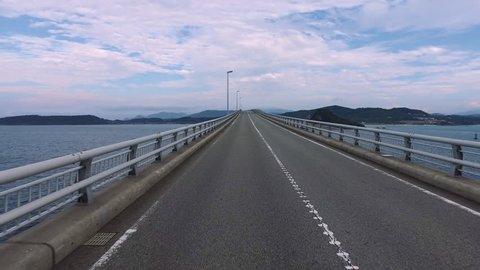 "Driving shot of empty, straight road over ocean ""Tsunoshima bridge"""