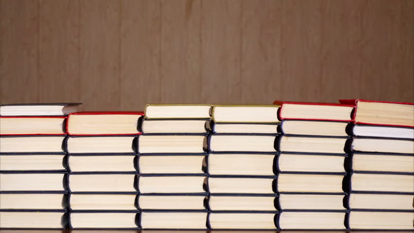 Books timelapse. Stacked books on wooden background. Time lapse of a growing stack of hardcover books