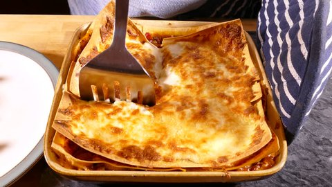 A dish of lasagne, straight from the oven, is sliced with a steel spatula.