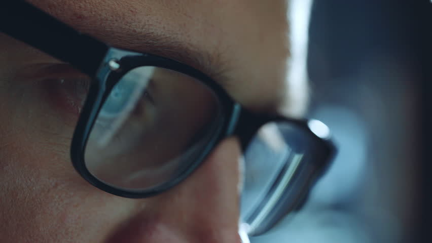 Closeup of young hipster guy wearing glasses and working at night via laptop at modern office, closeup of male eyes, reflections in glasses, work process | Shutterstock HD Video #28294075
