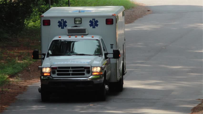 Stock footage Zoom Close Up of an ambulance emergency driving toward camera.