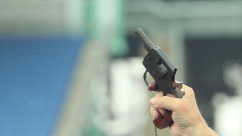 man's hand firing starting gun in slow motion with smoke in stadium