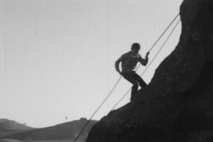 1960s: Young boys abseil down a cliff in home video footage from the 1960s by environmentalist David Brower, after which they go exploring through the trees with a woman who might be their mother.
