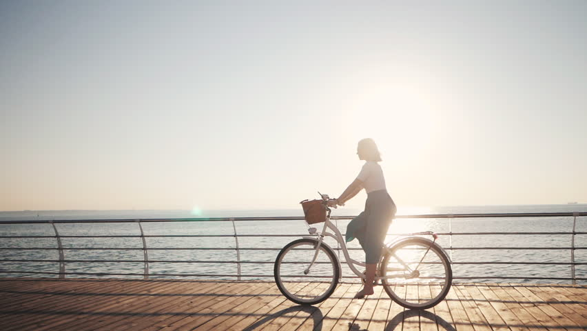 Young attractive woman riding vintage bike near the sea during sunrise or sunset. Slow motion.