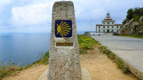 A pointer for the orientation of the Camino de Santiago pilgrims in Cape Finisterre. Finish zero Kilometers. In the background a lighthouse (faro) and an ocean. buen camino peregrino. video footage.