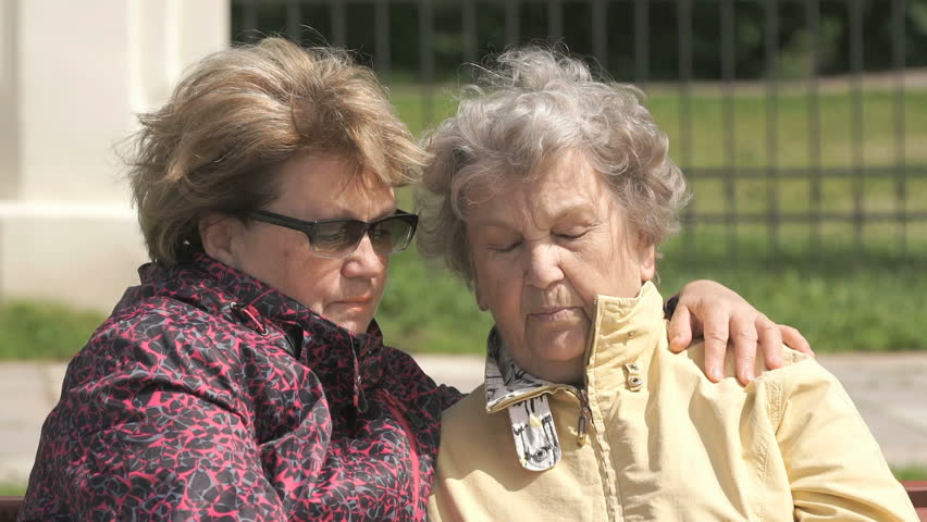Two women sit and talk outdoors. One woman aged 80s dressed in a yellow jacket, looks at the results of physical activity using a wristband fitness tracker outdoors.
