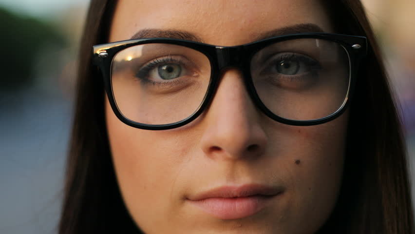Face portrait of beautiful young woman in glasses looking at the camera and taking off glasses outdoors in the city street. Close up