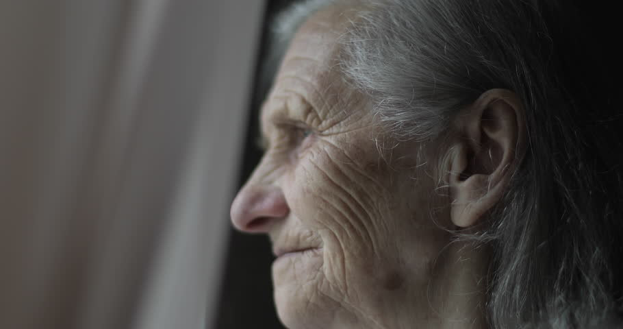 Close-up face of sad old woman with deep wrinkles. Grandmother with gray hair looks out the window and smile. 4K footage.