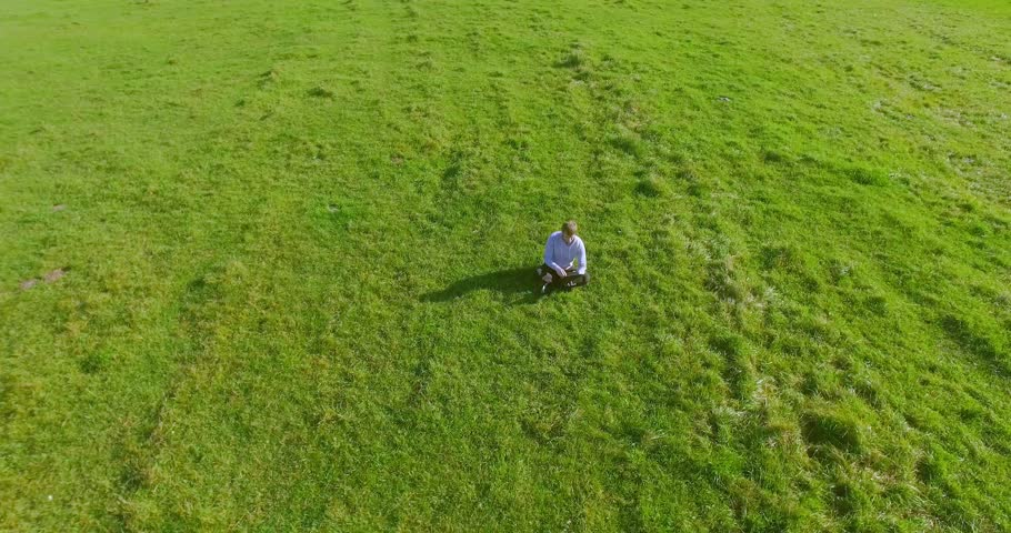 UHD 4k aerial view. Low orbital flight over businessman sitting on green grass with notebook (pad) at yellow rural wheat field. Radial movement. | Shutterstock HD Video #28408645