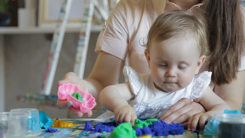 kid girl and mom play with plasticine in the art studio
