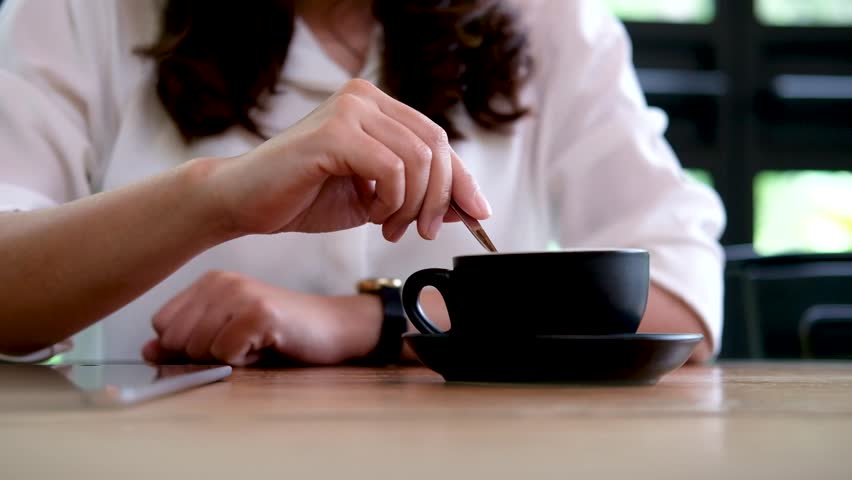 A woman holding coffee spoon to stirring hot coffee on wooden table and drinking in cafe - 4K stock video clip
