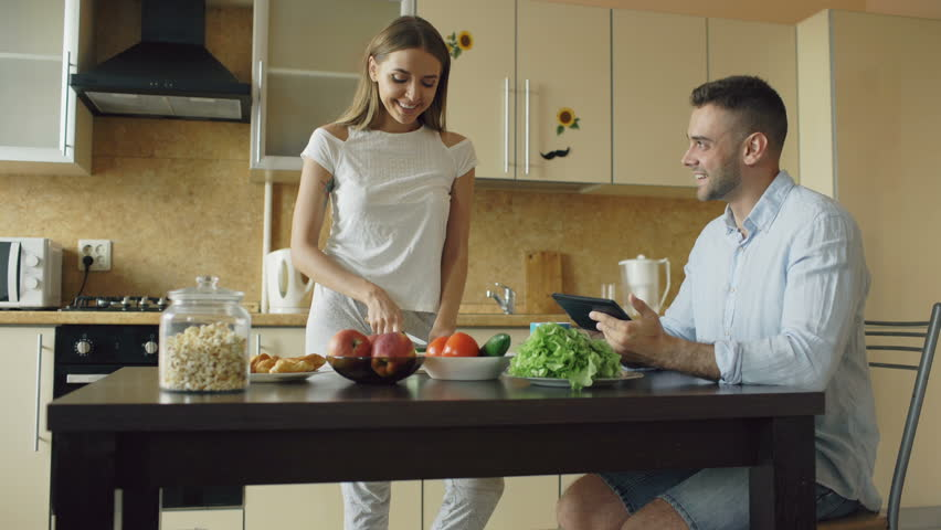 Tilt Up Of Attractive Couple Chatting In The Kitchen Early Morning.  Handsome Man Using Tablet