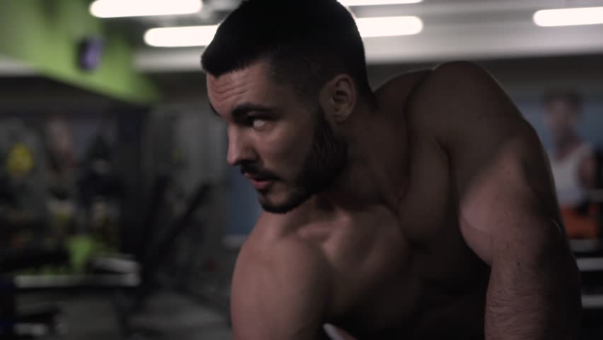 Strong Young Man with Naked Torso Exercising With Dumbbells in Gym. Male Bodybuilder Doing Back Exercises. Medium shot. | Shutterstock HD Video #28466155