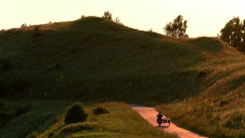 Motorcycle with a sidecar (tricycle) moves down the road of hilly terrain - Sunset