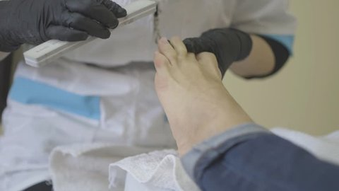 Nail shaping on the legs with emery board. Caring about the girl legs pedicure, polish, beautiful lights. Professional pedicure in the salon. Peeling feet pedicure procedure.