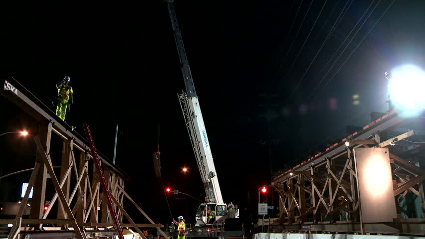 Los Angeles, California-2010s: Construction workers work on a freeway overpass at night in Los Angeles.