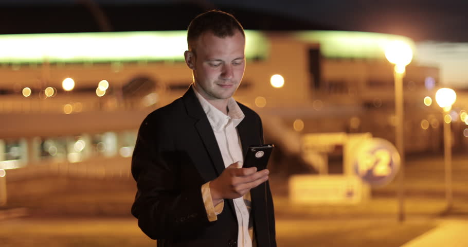Handsome young business man using mobile phone smiling happy wearing suit jacket outdoors. Man sms texting using app on smart phone at night in city. 4K footage. | Shutterstock HD Video #28511335