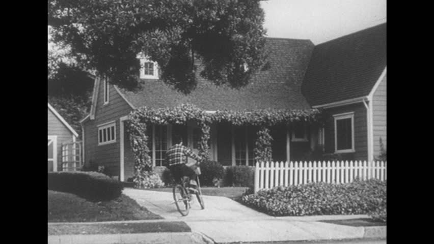 1950s: Paperboy rides bicycle into driveway. Paperboy throws newspaper onto house porch