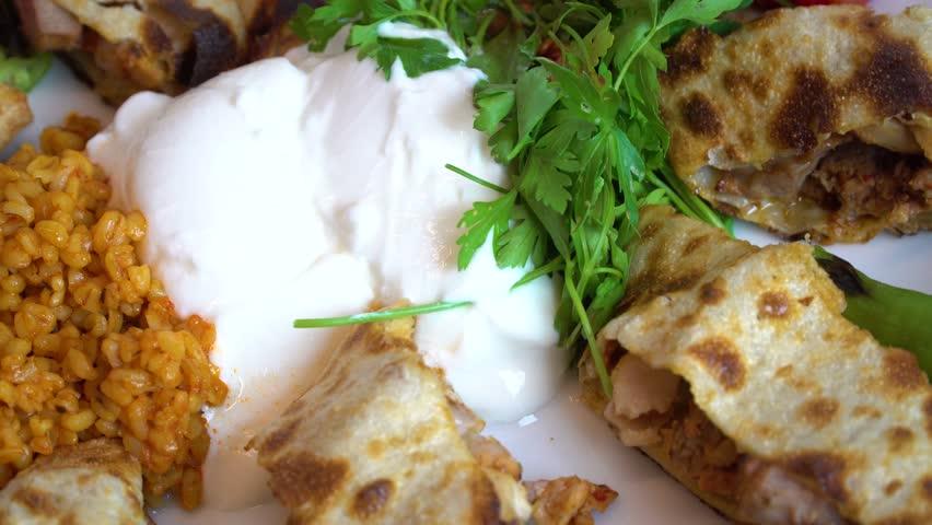 Turkish and Arabic Traditional Ramadan Food Kebab Beyti Sarma with Yogurt, serving lavash bread inside adana shish kebab. Rotating shot.