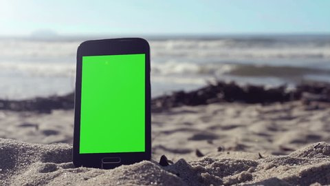 Generic black smart phone with green screen on the beach in Brazil, ready to key and replace.