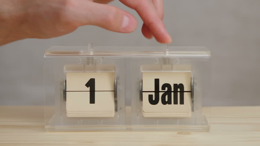 Close-up on a man changing dates on retro calendar from December 31 to January 1 on a wooden table. Filmed with studio light on a gray background. | Shutterstock HD Video #28553695