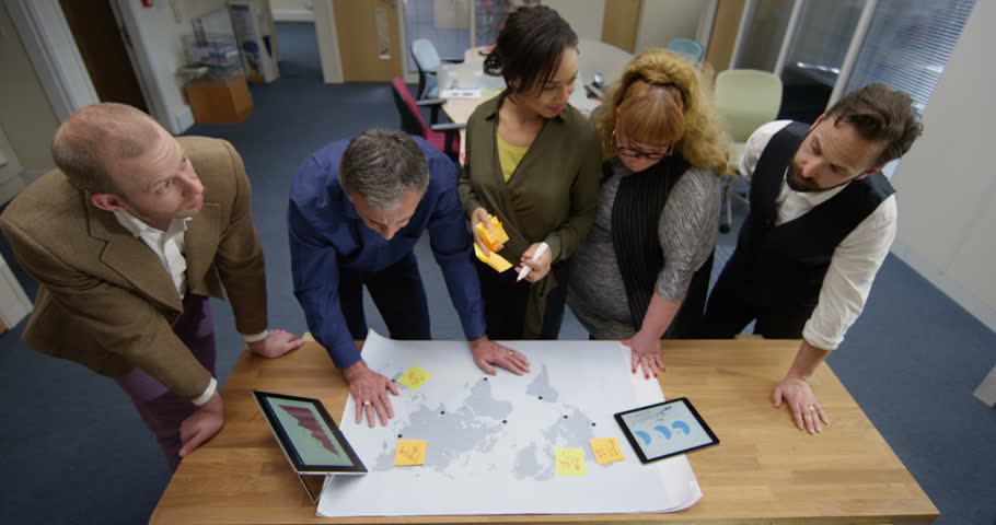 4K Business team in a meeting, looking at world map & analyzing financial data. Slow motion.   Shutterstock HD Video #28558375