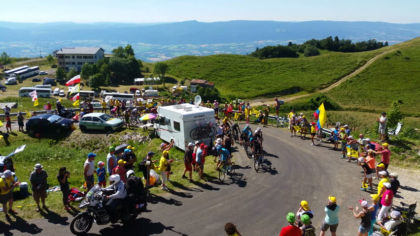 COL DU GRAND COLOMBIER,FRANCE-JUL 17: The peloton including Chriss Froome in Yellow Jersey climbing the road to Col du Grand Colombier in Jura Mountains during the stage 15 of Tour de France 2016. UHD