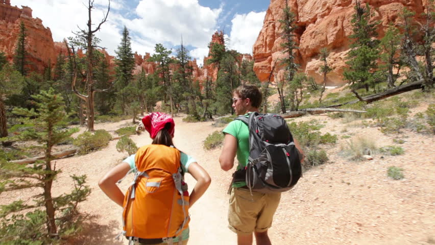 Hiking backpackers on hike in beautiful landscape in Bryce Canyon National park trekking smiling happy together. Multiracial couple, young Asian woman and Caucasian man in Utah, USA. | Shutterstock HD Video #2856739