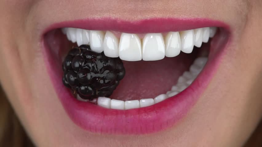 Slow motion close up: The young girl bites a blackberry. Minimally invasive porcelain veneers/ smile/ porcelain veneers color bleach