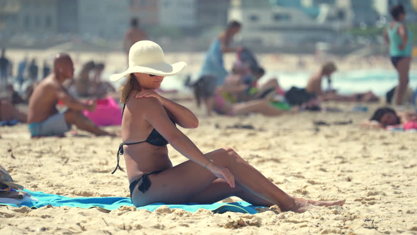 Sexy woman using sun lotion. Girl sunbathe on crowded beach