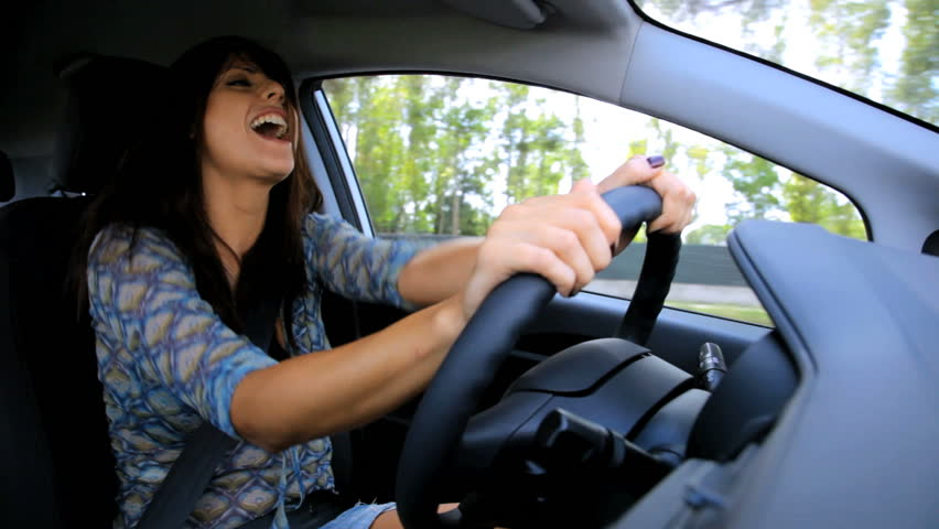 Happy woman singing and dancing while driving car