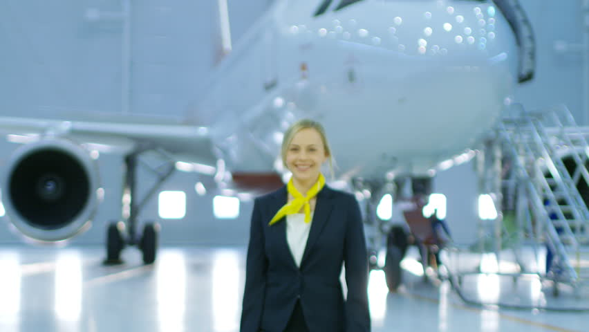 In a Aircraft Maintenance Hangar Young Beautiful Blonde Stewardess/ Flight Attendant Moves on Camera and Smiles Charmingly. In the Background Brand New Airplane is Visible.Shot on RED EPIC-W 8K Camera