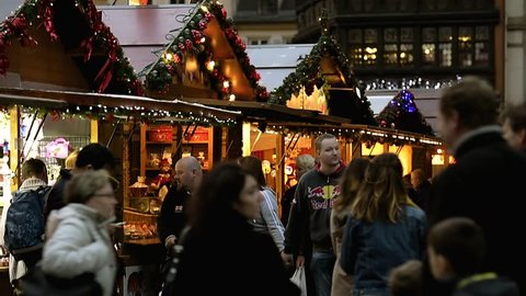 STRASBOURG, FRANCE - CIRCA 2017: Tourist couple spotted in crowd admiring the Christmas market stall with toys people and Christmas decorations food in central Strasbourg, Alsace, France market
