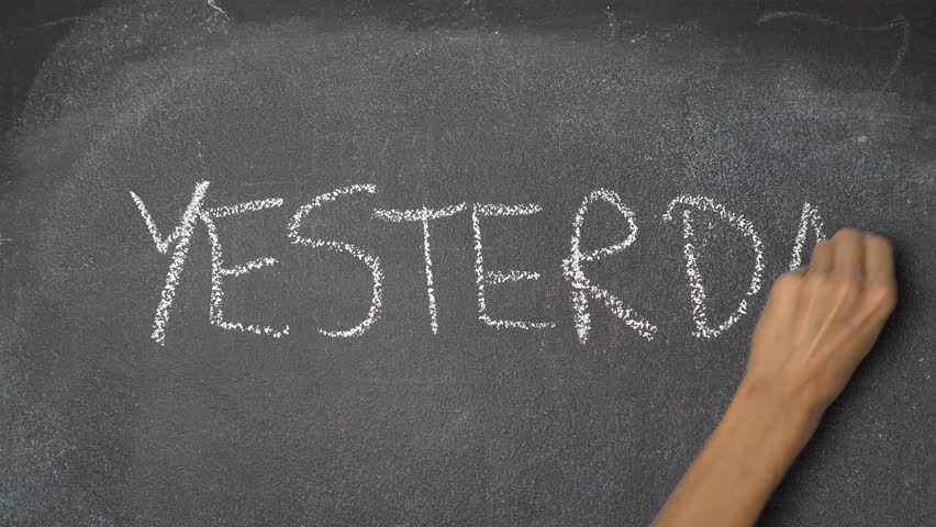 "Woman's hand writing ""TODAY, YESTERDAY, TOMORROW"" with white chalk on blackboard"