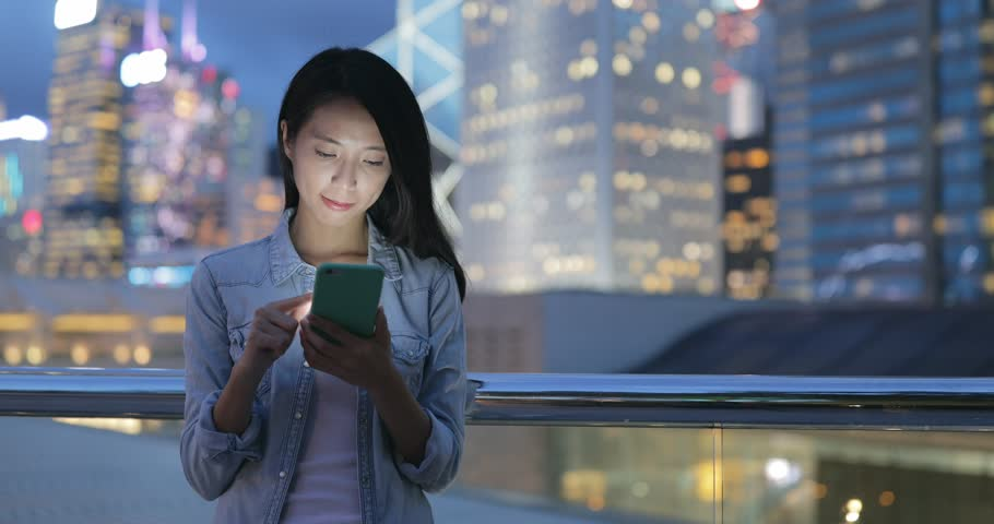 Young woman looking at mobile phone at night