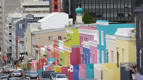 CAPE TOWN, SOUTH AFRICA CIRCA JULY 2017, view of Bo Kaap Wale street pastel colored houses perspective with top of mosque tower and city buildings behind with cars & people in street