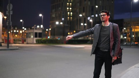 Young handsome businessman in glasses hitchhiking in a night street. He is wearing glasses and a suit. Locked down real time medium shot