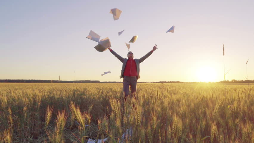 Businessman in a suit on a wheat field throws a stack of documents up and triumphantly throws up his hands, slow motion