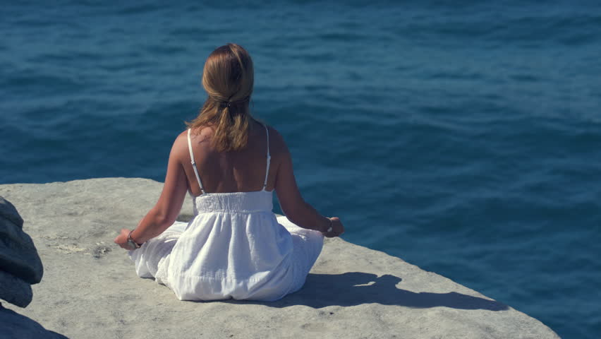 Woman meditating on a cliff over the ocean, Yoga on the rock