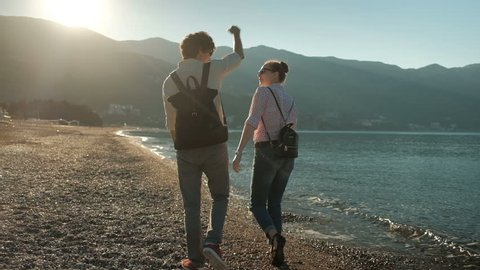 Couple walks along the beach in evening on a background of mountains. Two people in jeans walk along the seashore before sunset over the hills. They embrace and enjoy a walk in the warm summer. Behind