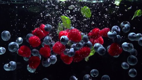 Raspberries, Blueberries and fresh mint leaves splashing into water on black background. Falling fresh fruits and berries in water. Organic berry, healthy food, diet 4K UHD video 3840X2160 slow motion